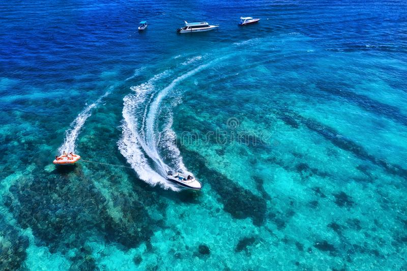 Yachts at the sea in Bali, Indonesia. Aerial view of luxury floating boat on transparent turquoise water at sunny day. Summer seas. Cape from air. Top view from royalty free stock images