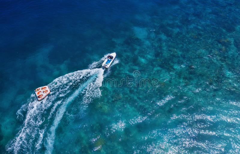 Yachts at the sea in Bali, Indonesia. Aerial view of luxury floating boat on transparent turquoise water at sunny day. Summer seas. Cape from air. Top view from stock photos