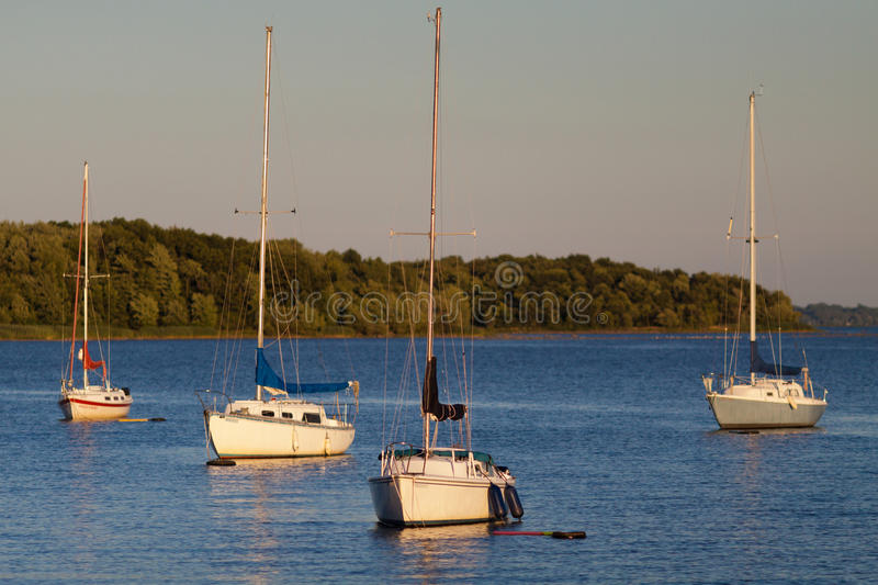 Yachts at sunset stock images