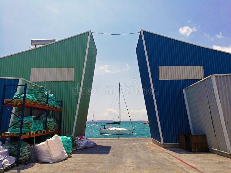 Yachtsegeln zurück zu Hafen unter Struktur stockfotos