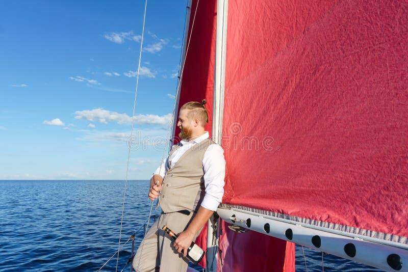 'yachtsman' com uma garrafa do vinho espumante fotos de stock royalty free