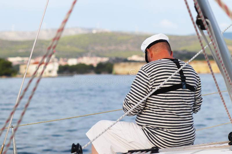 Yachtsman in marine clothing looking into the distance sitting on board a sailing yacht. Sea fishing from the ship. Peaceful state royalty free stock photos