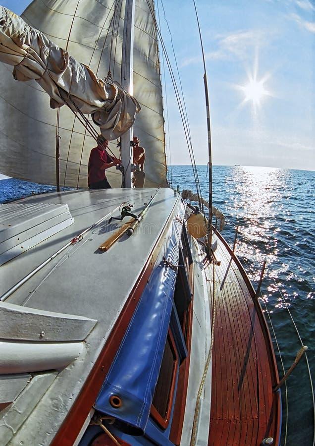 Yachtsport auf dem Schwarzen Meer Eine Yacht segelt in Richtung zum schönen Seesonnenuntergang Vertikaler szenischer Sommermeerbl lizenzfreies stockbild