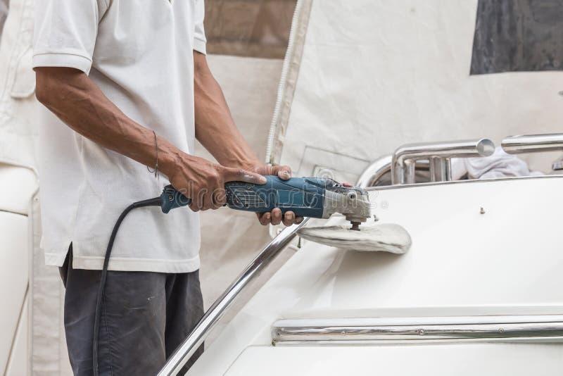 Yachtwartung Eine Mannpolierseite des weißen Bootes in lizenzfreie stockbilder