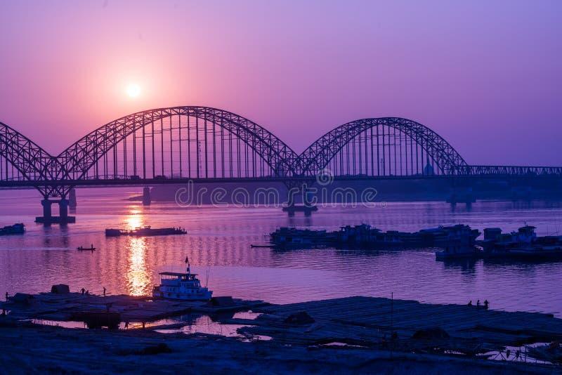 Yadanarbon bro på solnedgången över den Ayeyarwady floden arkivfoto