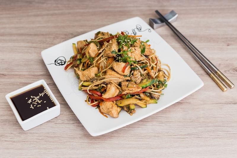 Yakisoba with soy sauce on a wooden table royalty free stock photo