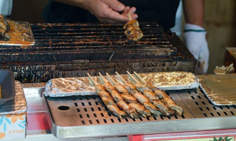Yakitori giapponese tradizionale del pollo - la carne di pollo grigliata è servito sugli spiedi, al mercato dell'alimento della v fotografia stock