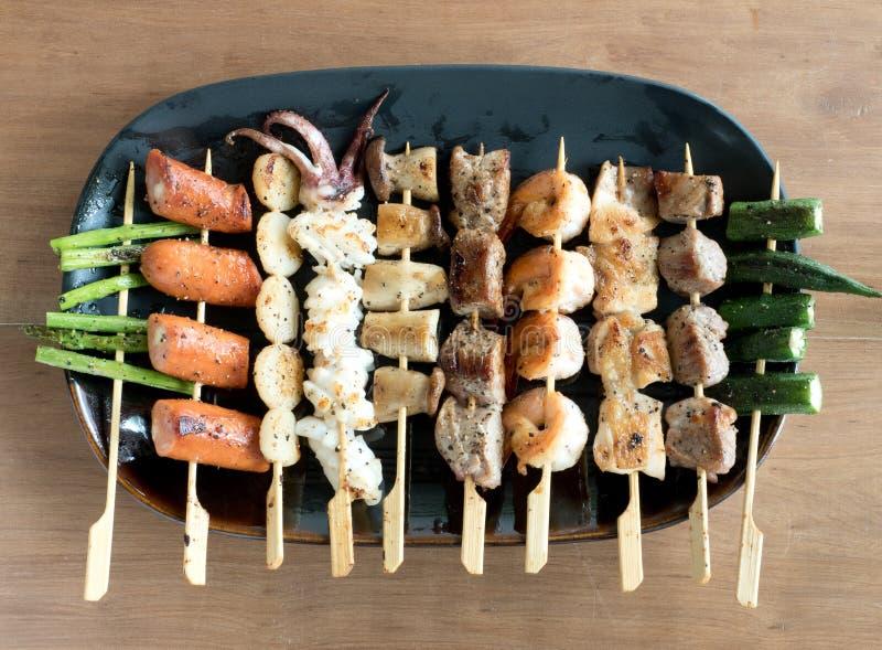 Yakitori: Japan tugga-storleksanpassade matsteknålar: sparris, korv, kammussla, tioarmad bläckfisk, champinjon, räkor, höna, gris arkivfoton