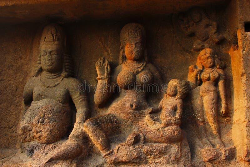 Yaksha Jambhala zit met zijn vrouw, Hariti, die één van haar vijf honderd kinderen op haar overlapping, Hol 8, Ellora Caves houdt stock afbeelding