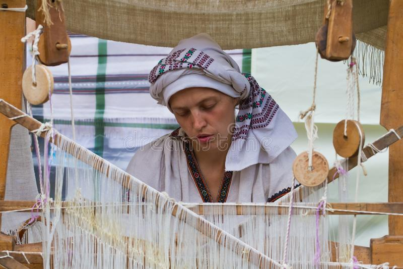 Portrait of woman weaver working at ancient loom, making carpet royalty free stock photography