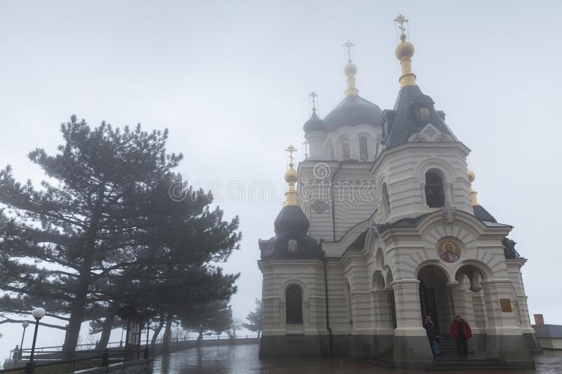 Church of Christs Resurrection, Yalta, Crimea. Yalta, Crimea - March 26, 2017:  Church of Christs Resurrection at foggy spring day. Ordinary people are near the stock photography