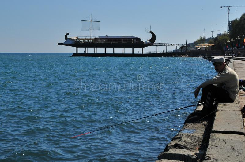 Old man fishing on shore with Apelʹsyn Boat restaurant in the back. stock images