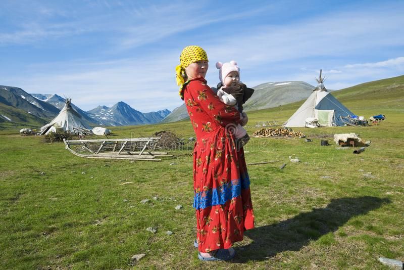 The female Hanty with the child on hands against the background of a settlement of reindeer breeders. YAMAL, RUSSIA - AUGUST 27, 2018: The female Hanty with the royalty free stock photos