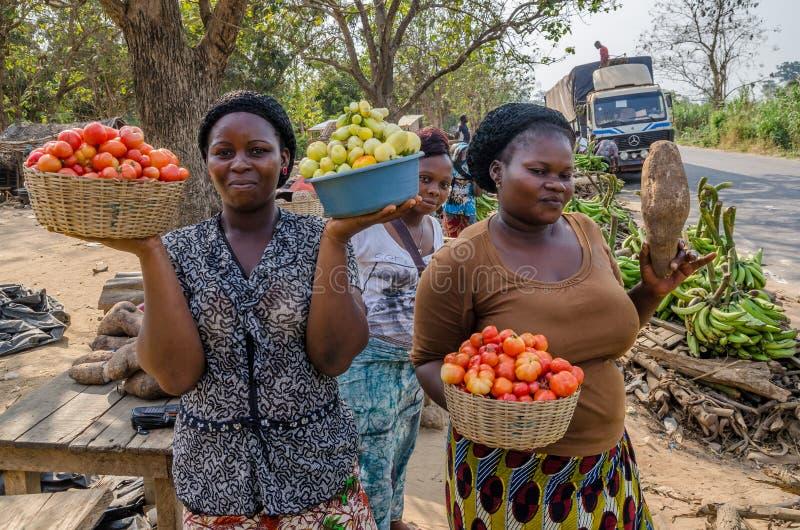 Yamoussoukro Elfenbenskusten - Januari 31,2014: Oidentifierade afrikanska kvinnor som framlägger deras grönsaker på vägmarknaden royaltyfri foto