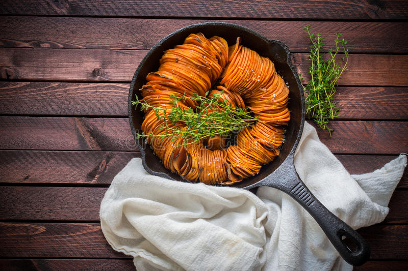 Yams in cast iron pan. Spiral yams in cast iron pan with honey, olive oil, sea salt with thyme stock photography