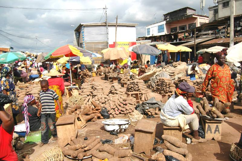 Yams for sale in market in Kumasi, Ghana. Kumasi, Ghana: 21st July 2016 - piles of yams for sale in a market in Kumasi, West Africa royalty free stock image