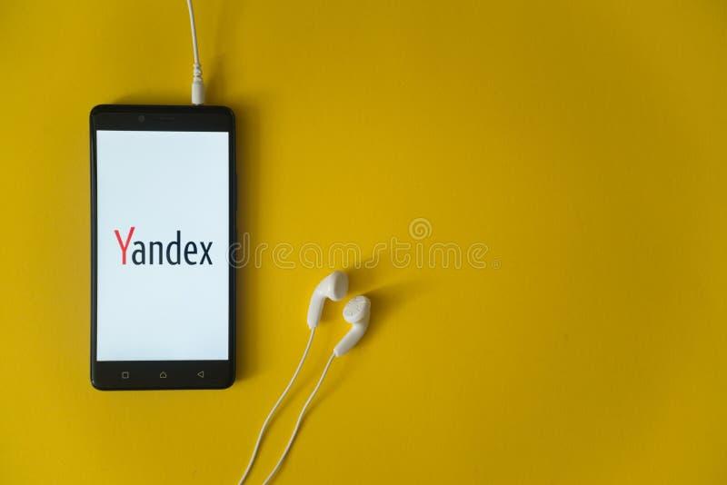 Yandexembleem op het smartphonescherm op gele achtergrond stock foto