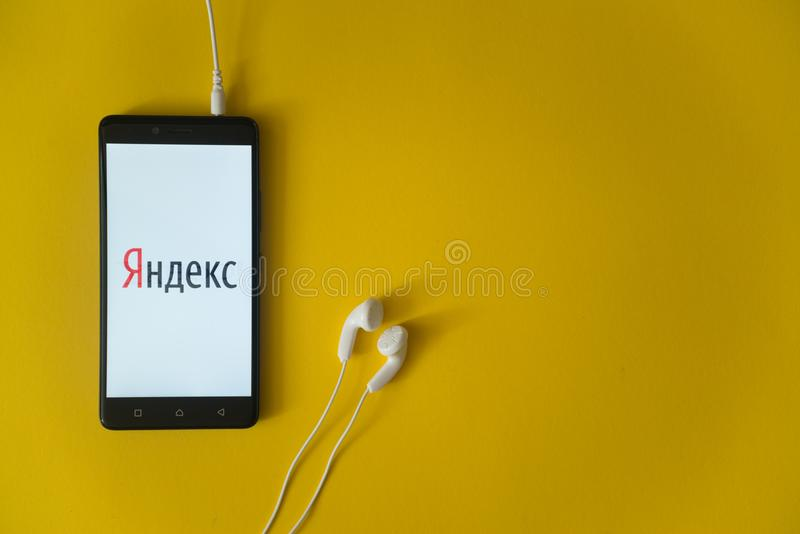 Yandexembleem op het smartphonescherm op gele achtergrond stock afbeelding