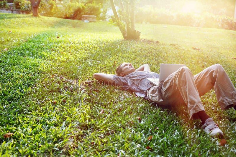 Yang biznesowy mężczyzna relaksuje outdoors z laptopem zdjęcia stock