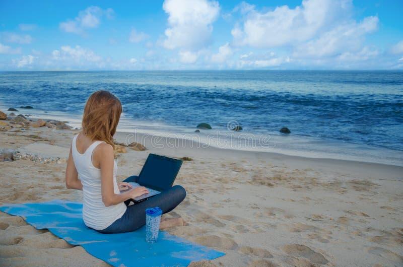 Yang kvinna med bärbara datorn vid havet arkivfoton