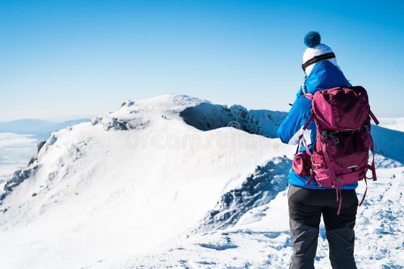 Yang woman walking on snowy mountains royalty free stock photo