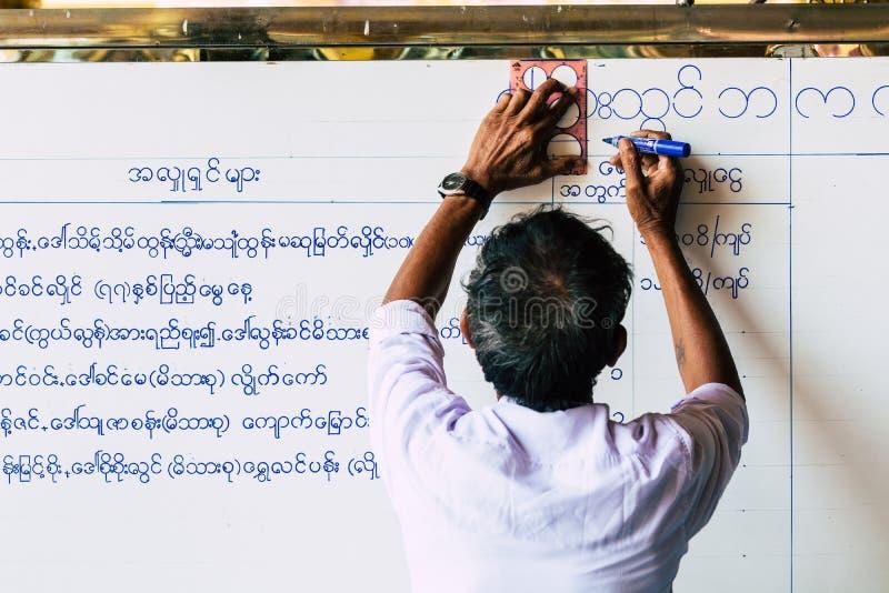 Yangon, το Μιανμάρ - το Μάρτιο του 2019: Βιρμανός πρόγραμμα τελετής ναών γραψίματος ατόμων στο λευκό πίνακα στοκ εικόνα με δικαίωμα ελεύθερης χρήσης