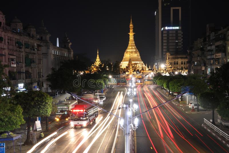 Night time and speed of light at golden octagon of Sula pagoda located in the heart of downtown Yangon with building and many cars. Yangon, Myanmar Feb 21, 2019 stock images
