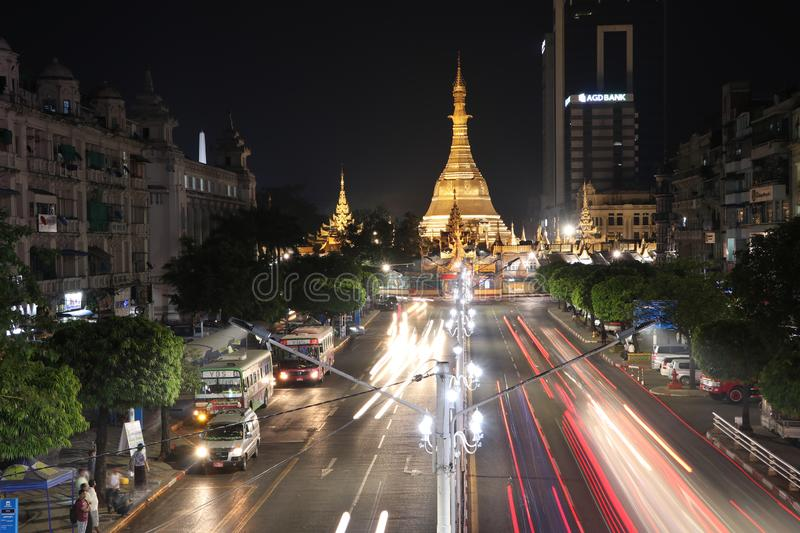 Night time and speed of light at golden octagon of Sula pagoda located in the heart of downtown Yangon with building and many cars. Yangon, Myanmar Feb 21, 2019 royalty free stock photos