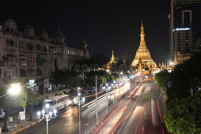 Night time and speed of light at golden octagon of Sula pagoda located in the heart of downtown Yangon with building and many cars. Yangon, Myanmar Feb 21, 2019 royalty free stock photography