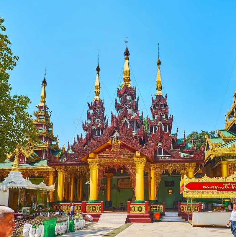 Rakhine Tazaung Shrine of Shwedagon, Yangon, Myanmar. YANGON, MYANMAR - FEBRUARY 27, 2018: The intericate wooden carvings on pyatthat roof of Rakhine Tazaung royalty free stock images