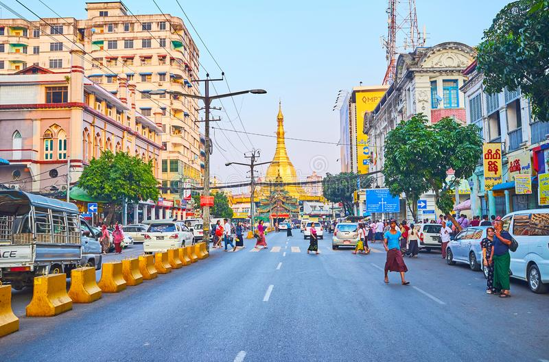 In Downtown of Yangon, Myanmar. YANGON, MYANMAR - FEBRUARY 14, 2018: The view on golden Sule Pagoda from the busy Maha Bandula road, one of the central streets royalty free stock photos
