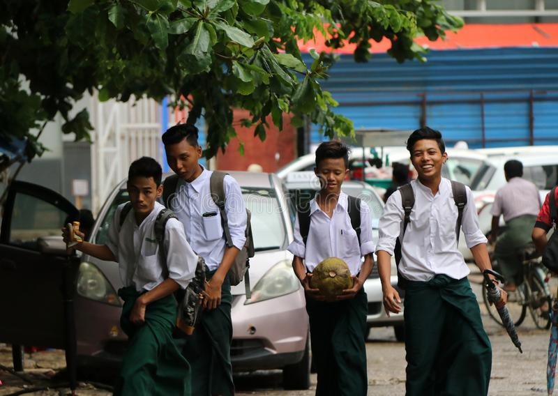 Four collegians in Myanmarese uniform of college white shirt and green Long Yi walking homing on the street after school program stock image