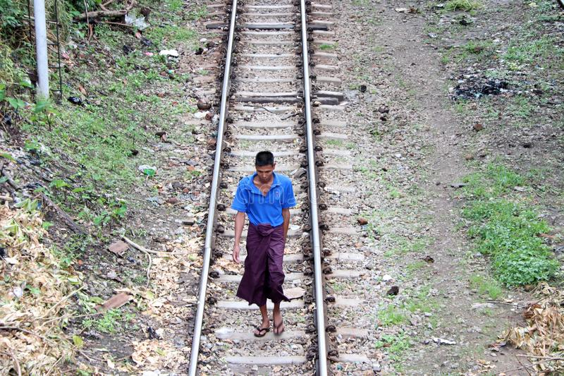 Myanmarese man villager in short sleeve T shirt and Long Yi walking on the railroad tracks. stock images