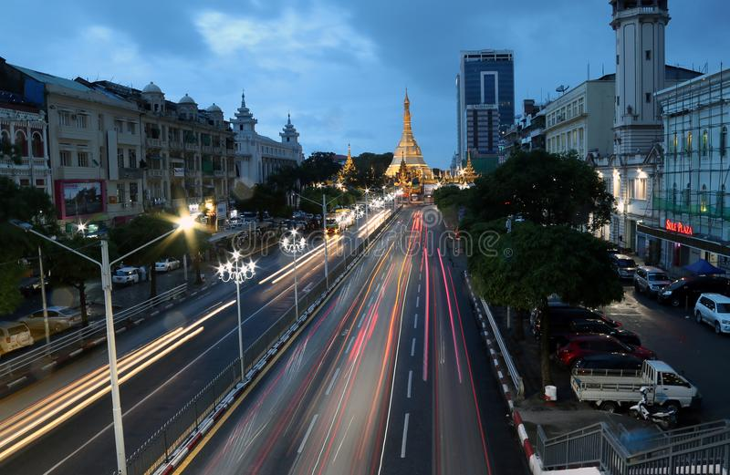 Twilight time and speed of light at golden octagon of Sula pagoda located in the heart of downtown Yangon. Yangon, Myanmar June 6, 2018: Twilight time and speed stock photos