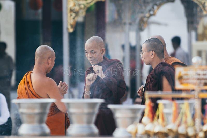 Yangon, Myanmar - Maart 2019: De boeddhistische monniken hebben een bespreking in Shwedagon-complexe pagodetempel royalty-vrije stock foto's