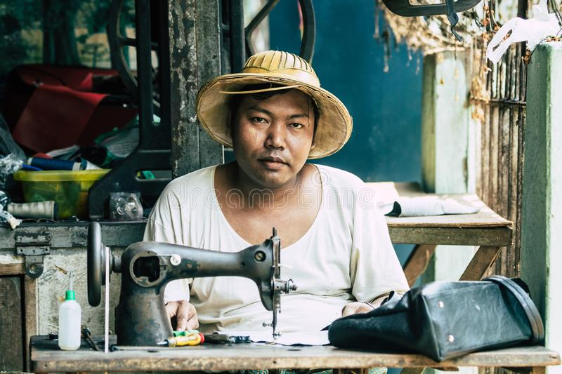 Yangon, Myanmar - March 2019: Asian man in straw hat behind mechanical sewing machine in the street tailor shop stock photo