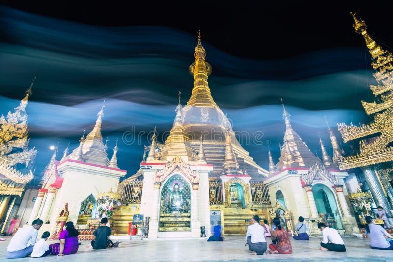 Yangon Myanmar - mars 2019: Folket ber p? den Sule pagoden i aftonen royaltyfri fotografi