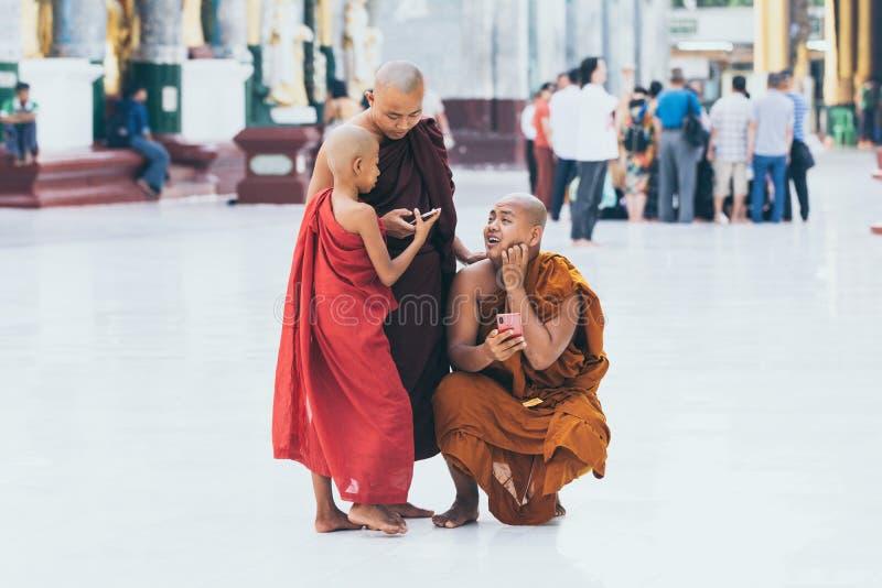Yangon Myanmar, Marzec, - 2019: młodzi Buddyjscy nowicjuszów michaelici z gadżetami w Shwedagon pagodowym świątynnym kompleksie zdjęcie royalty free