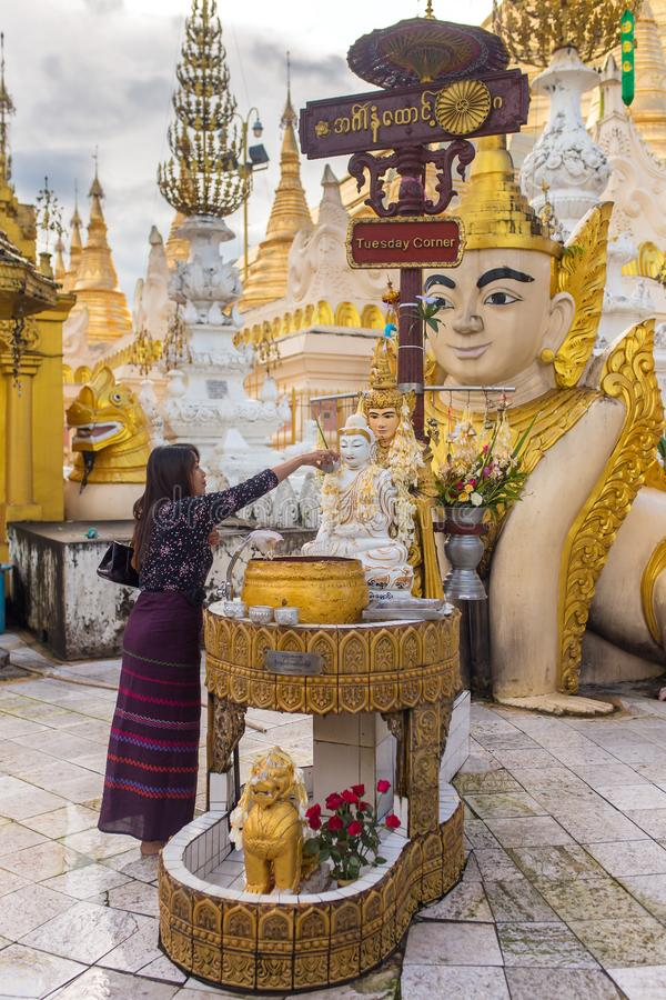 Unidentified burmese woman pouring water over the Buddha statue for blessing in Shwedagon pagoda in Yangon, Myanmar. Yangon, Myanmar - September 27, 2016 stock photo