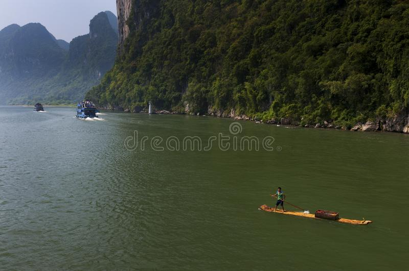 Chinese man in a raft and boats with tourists cruising in the Li River near the town of Yangshuo in China stock photo