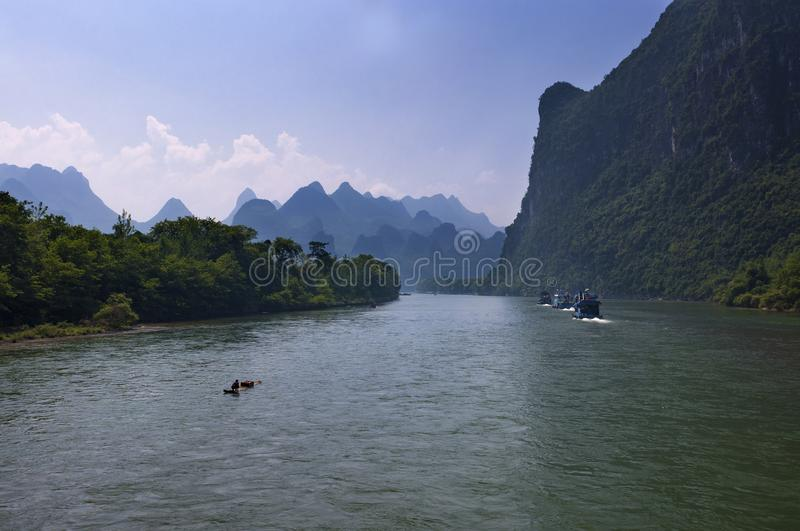 Traditional raft and boats with tourists cruising in the Li River near the town of Yangshuo in China royalty free stock photos