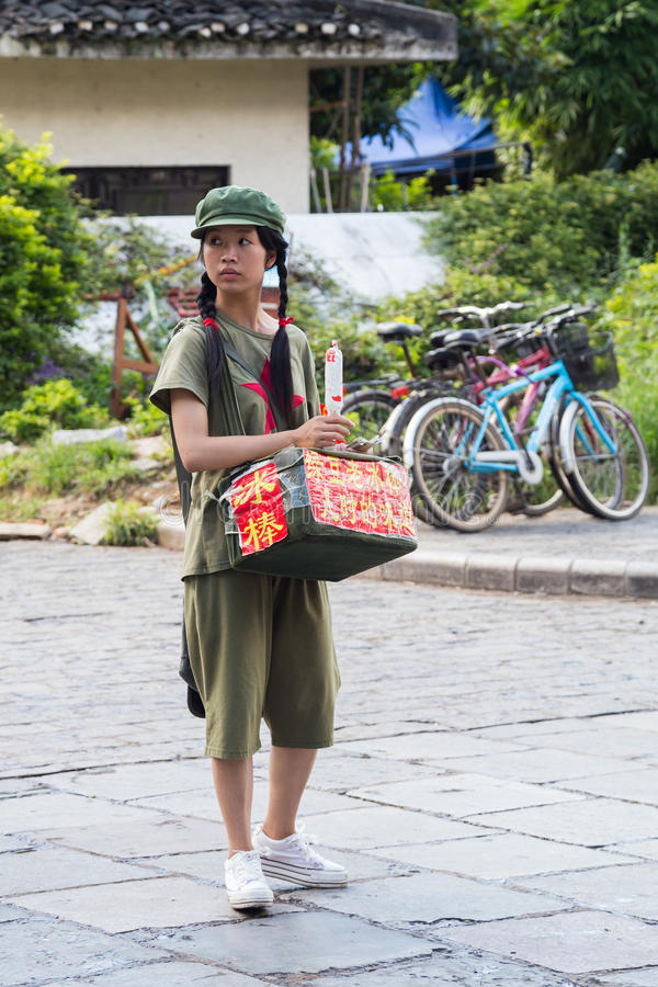 Yangshuo, China - circa im Juli 2015: Chinesisches junges Pioniermädchen verkauft Lebensmittel oder Andenken auf den Straßen der  lizenzfreie stockbilder