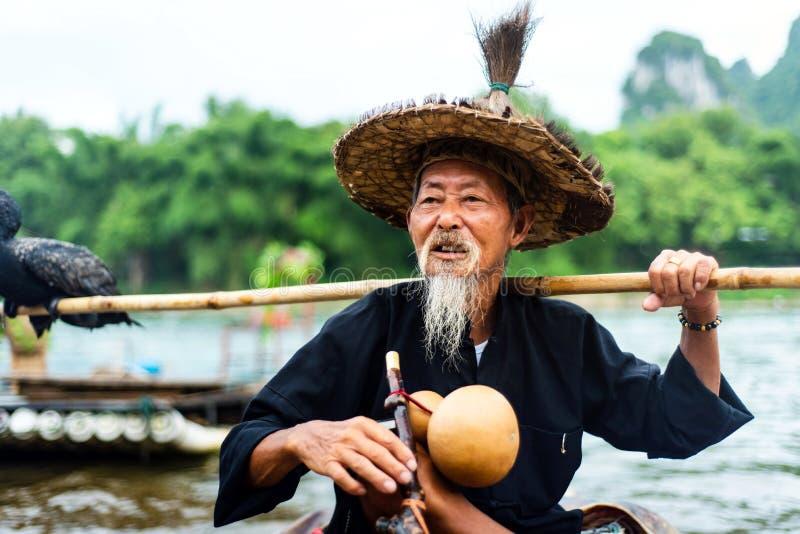 Yangshuo, China - 27 de julio de 2018: Pescador del cormorán en balsas de bambú en el río de Li en Yangshuo cerca de Guilin en Ch foto de archivo libre de regalías