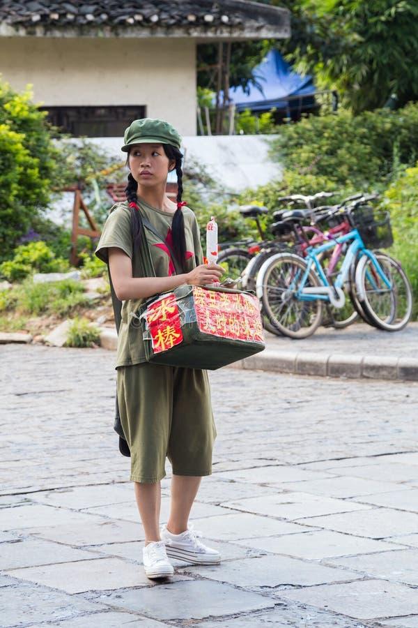 Yangshuo Kina - circa Juli 2015: Säljer den banbrytande flickan för kinesiskt barn mat eller souvenir på gatorna av den turist- s royaltyfria bilder