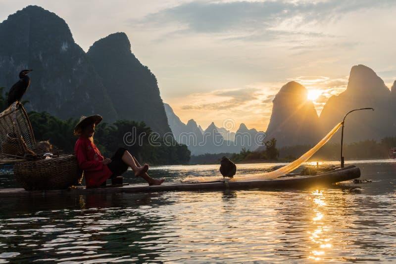 Yangshuo, paisaje de la puesta del sol de China en el río tranquilo con el aldeano encendido imagen de archivo libre de regalías