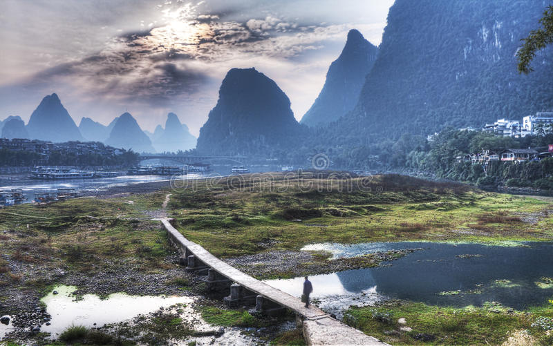 Yangshuo Scenery from China Guilin. Yangshuo Sunrise Scenery from China Guilin. Feature a man on boardwalk on his way to his daily routine. Yangshuo bridge, Page stock photo
