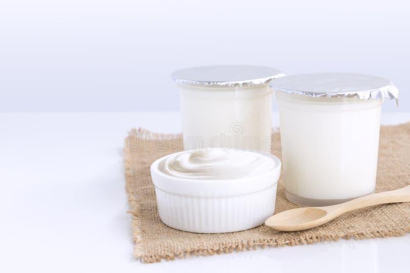 Yaourt aromatisé sain dans la tasse en plastique et la cuvette en céramique avec la cuillère en bois d'isolement sur la table bla image stock