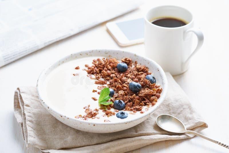 Yaourt avec la granola de chocolat, myrtille Petit déjeuner avec la tasse de café, mobile, journal sur le fond blanc, vue de côté images stock