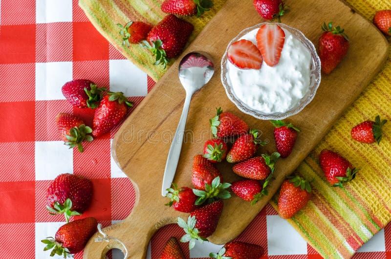 Yaourt blanc dans le petit bol en verre avec les fraises coupées sur le dessus, cuillère de thé de côté photo libre de droits