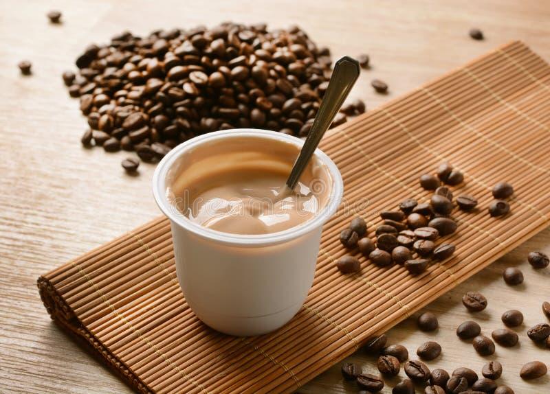 yaourt Café-assaisonné avec des grains de café autour photos stock